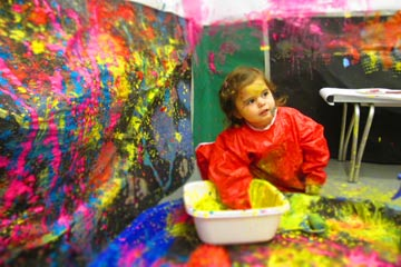 Little girl sitting on the floor painting in a room with paint splattered walls
