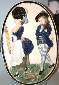 An oval plaque of a man looking at a woman