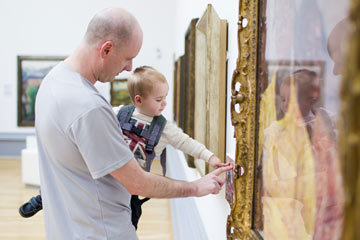 A father looks at a painting with his son