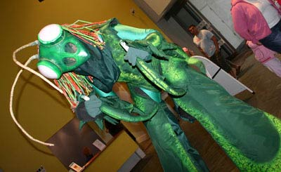 a stiltwalker in a green preying mantis outfit