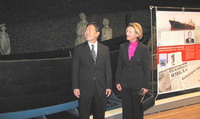 smartly dressed man and woman standing next to a wooden boat in a museum display