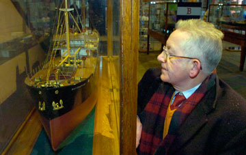 Stephen next to a model ship in a display case