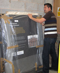 Richard Benjamin covering a museum display panel in bubble wrap