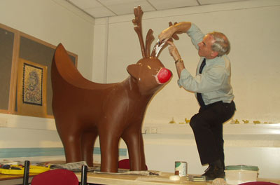 man painting a lamb sculpture with a banana shaped tail