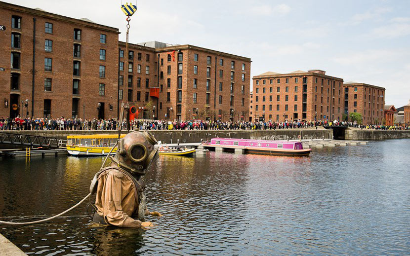 Enormous wooden puppet of a diver, standing in the water by the Albert Dock