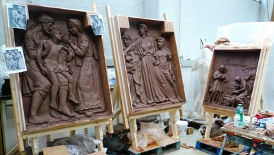 Three clay panels sculpted into scenes with figures in classical clothing
