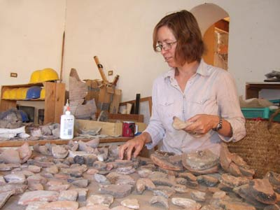 woman examining lots of pieces of ancient pottery on a table