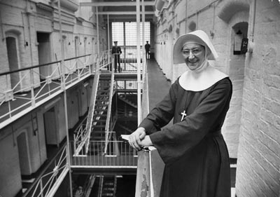 a nun standing by the balcony in a prison