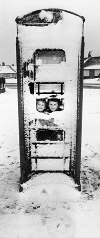 photo of 2 boys in a phonebooth covered in snow
