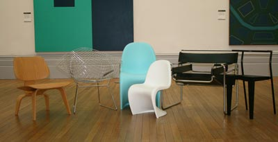 A row of different coloured contemporary chairs