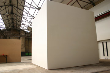 Large white cube in a warehouse