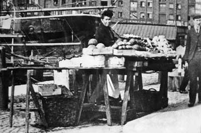 Black and white photo of a Black woman at a market stall in a town