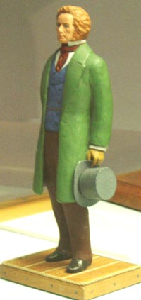 statue of a fair haired man in a green coat and carry a grey top hat