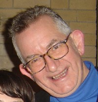 a smiling man wearing glasses