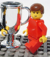 a photo of a lego man in red standing next to a lego trophy