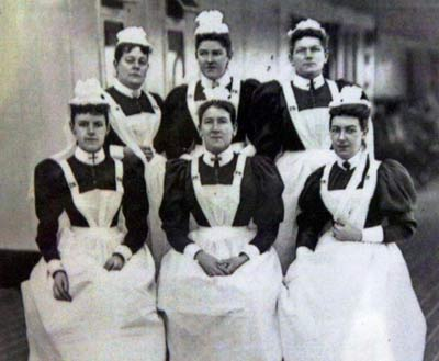 Black and white photo of six women in white aprons and hats posing on the deck of a ship