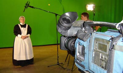 actress in maid costume being filmed in front of green screen