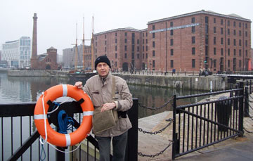 man standing by a life buoy in the Albert Dock