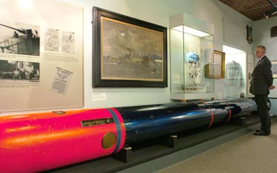 man in a museum standing next to a long torpedo, text panels and cases
