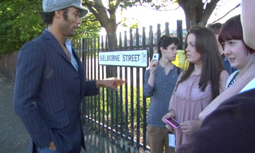 people talking by park railings and a 'Selborne Street' sign