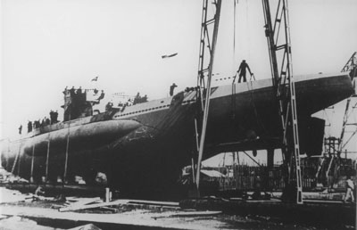 Black and white photo of a submarine being hoisted out of water.