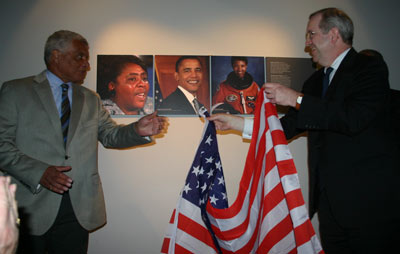 men revealing pictures on wall from behind an American flag