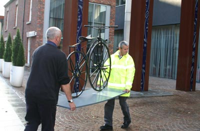 Two men carefully carry a very old bicycle into a building