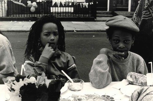 two children sitting at a table at a street party