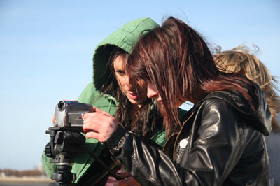 windswept girls filming with a small video camera on a tripod at the Liverpool waterfront