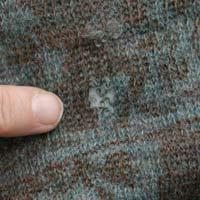 Close up of a hole in the woollen dress