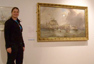 woman standing by a painting of sailing ships in a rough sea