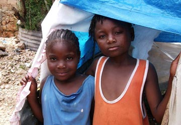 two Haitian children in a tarpaulin shelter
