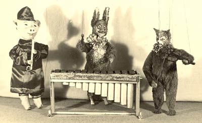 pig, wolf and cat marionettes playing instruments