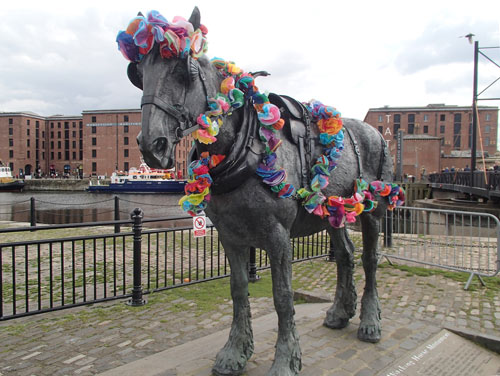 horse statue with garlands of paper flowers draped around it