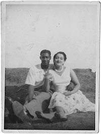 Young man and woman sitting with their arms round each other