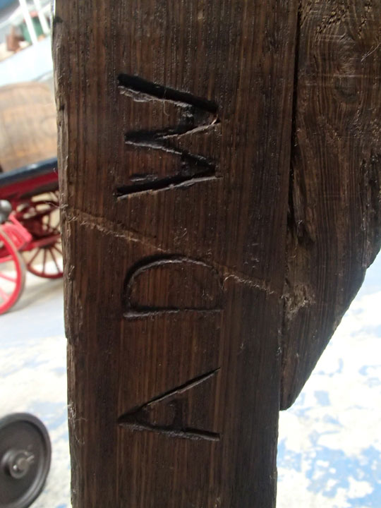 detail of 'ADW' carved into wooden cart