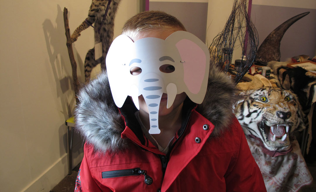 boy wearing paper elephant mask by a display including taxidermy animals and a tiger skin rug