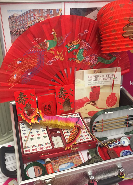 open suitcase containing Chinese memorabilia including fans, lanterns, photos and more