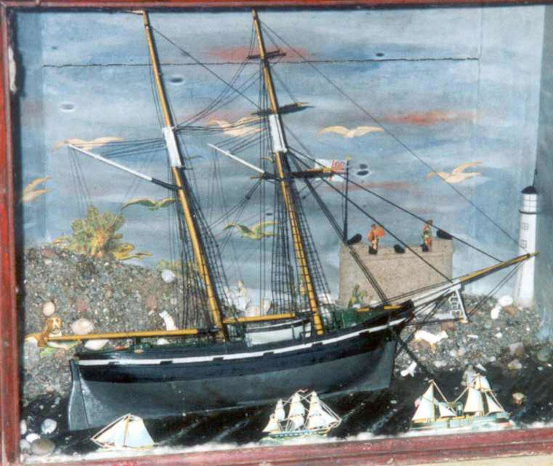 framed diorama of a sailing ship with a lighthouse, castle and other much smaller ships