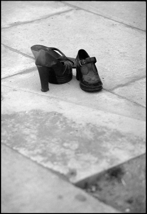 Three abandoned high heeled shoes on the pavement