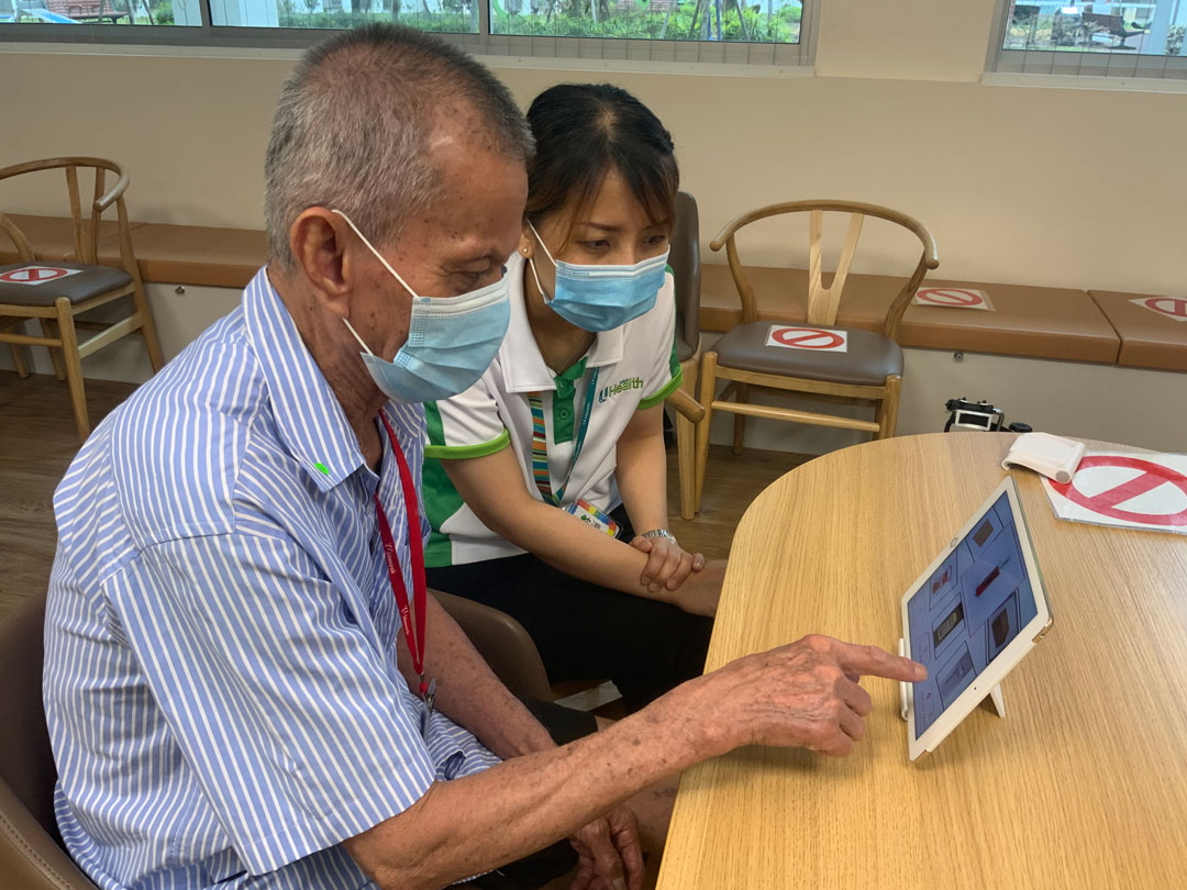 people wearing facemasks, using an ipad together