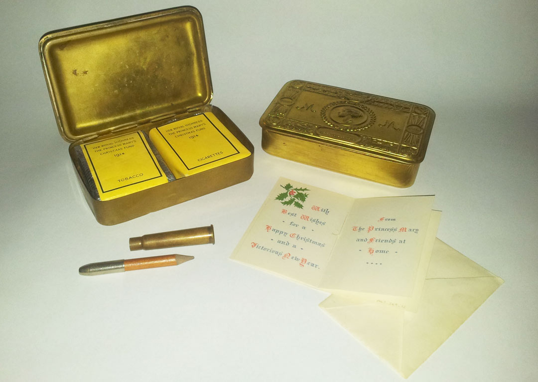 Tin box with a Christmas card, bullet and pencil
