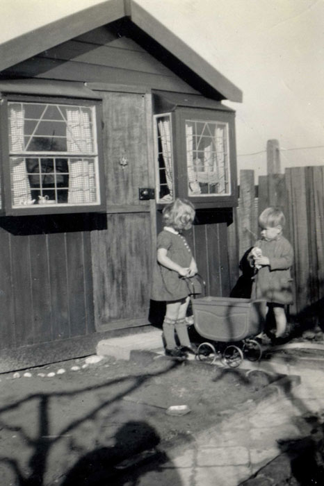 two small children by a large shed-like Wendy house