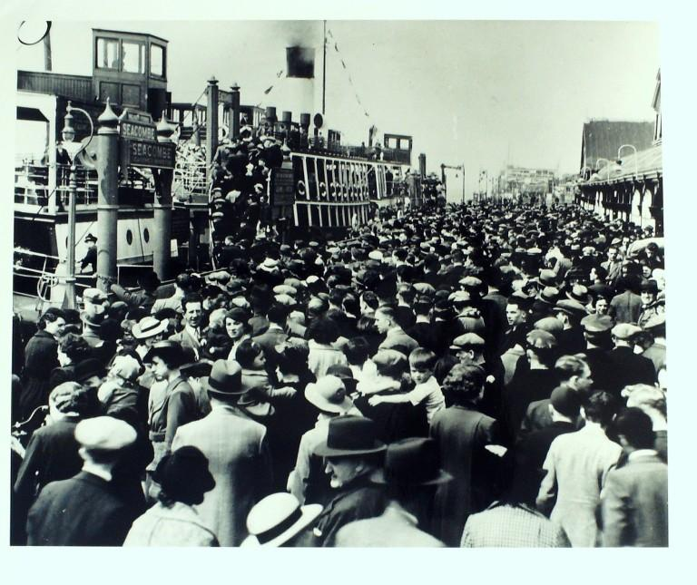 Photograph of crowded landing stage with passengers boarding ferry card