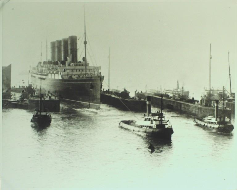 Photograph of Lusitania Entering Sandon Dock with tugs in attendance, Cunard Line card